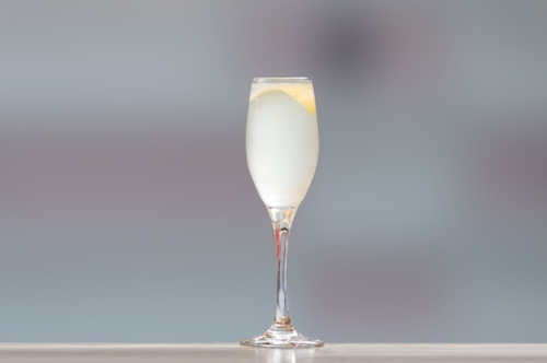 A French 75 in a champagne flute with a lemon twist